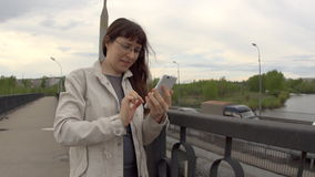 Uma jovem mulher em um revestimento branco usa um telefone na ponte da cidade video estoque