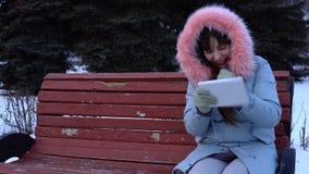 Uma jovem mulher em um revestimento morno usa uma tabuleta digital no parque no inverno video estoque