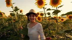 Uma jovem mulher em um vestido branco e em um chapéu de palha vai ao campo dos girassóis durante o por do sol filme