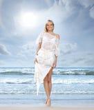 Uma jovem mulher em um vestido branco em um fundo da praia Imagem de Stock Royalty Free
