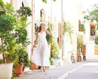 Uma jovem mulher em um vestido branco em umas férias Fotos de Stock Royalty Free
