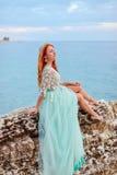 Uma jovem mulher em um vestido da hortelã senta-se em uma grande pedra na costa do mar de adriático imagens de stock