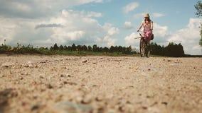 Uma jovem mulher em um vestido monta uma bicicleta no fundo de um campo na vila vídeos de arquivo