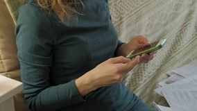 Uma jovem mulher em um vestido verde senta-se em um sofá com um portátil, usos um telefone e um cartão plástico, trabalhos, estud vídeos de arquivo