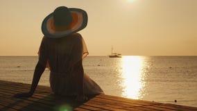 Uma jovem mulher encontra o nascer do sol no cais Senta e olha o sol e o navio no mar Sonhos e romance imagem de stock