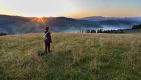 Uma jovem mulher encontra um alvorecer em um monte do prado nas montanhas Carpathian Foto de Stock