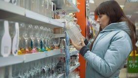Uma jovem mulher escolhe pratos na loja filme