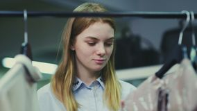 Uma jovem mulher escolhe a roupa em um boutique elegante, uma menina examina as camisetas que pesam em ganchos video estoque