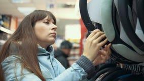 Uma jovem mulher escolhe uma tampa para dirigir o carro vídeos de arquivo