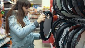 Uma jovem mulher escolhe uma tampa para dirigir o carro video estoque
