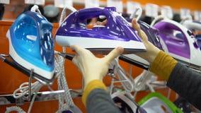 Uma jovem mulher escolhe um ferro em uma loja do aparelho eletrodoméstico filme