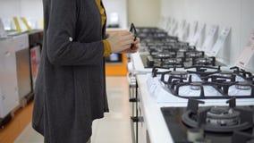 Uma jovem mulher escolhe um fogão de gás em uma loja do aparelho eletrodoméstico video estoque