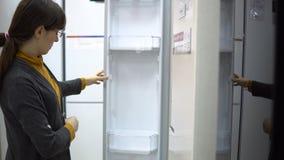 Uma jovem mulher escolhe um refrigerador em uma loja do aparelho eletrodoméstico video estoque