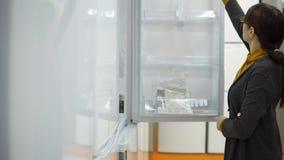 Uma jovem mulher escolhe um refrigerador em uma loja do aparelho eletrodoméstico filme