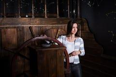 Uma jovem mulher está ao leme do navio e olha no foto de stock royalty free