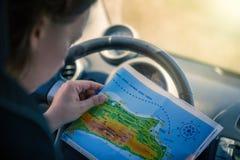 Uma jovem mulher está conduzindo um carro e está olhando o mapa Mapa da ilha grega de Kos A capital de Kos imagem de stock