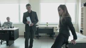 Uma jovem mulher está dançando no escritório sobre contra as janelas A mulher de negócios loura começou a dançar em torno do trab filme