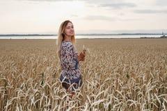Uma jovem mulher está em um campo de trigo fotografia de stock