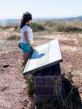 Uma jovem mulher está em um monte e examina um mapa de Golan Heights Imagens de Stock