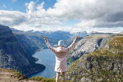 Uma jovem mulher está em um penhasco no fundo das montanhas bonitas fotografia de stock royalty free