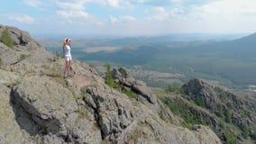 Uma jovem mulher está estando na borda de um penhasco impressionante da montanha, zumbido da zorra vídeos de arquivo