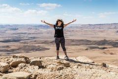 Uma jovem mulher está extensamente de espalhamento suas mãos na borda do penhasco na perspectiva do deserto de Judean em Israel imagens de stock