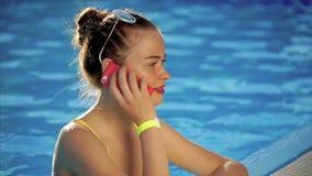 Uma jovem mulher está falando no telefone na água, ela está chamando um amigo filme