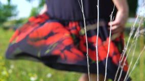 Uma jovem mulher está girando em um prado em um vestido video estoque