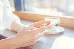 Uma jovem mulher está guardando um telefone em uma tabela em um café Imagem de Stock Royalty Free