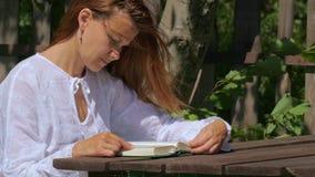 Uma jovem mulher está lendo um livro ao sentar-se em uma tabela de madeira em um parque vídeos de arquivo