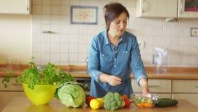 Uma jovem mulher está preparando uma dança da sopa entre um fogão e uma tabela Grande humor Cozinha home vegetarianism Saudável filme