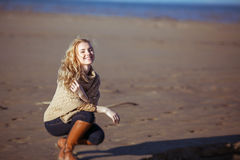 Uma jovem mulher está sentando-se em no seus quadris e sorriso Fotos de Stock