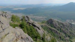 Uma jovem mulher está sentando-se na borda de um penhasco impressionante da montanha das montanhas, efeito do zumbido da zorra vídeos de arquivo