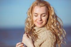 Uma jovem mulher está sorrindo com seus olhos fechados Imagem de Stock Royalty Free