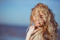 Uma jovem mulher está sorrindo, seu cabelo que pendura para baixo em sua cara Foto de Stock
