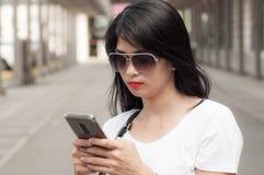 Uma jovem mulher está usando um telefone esperto foto de stock
