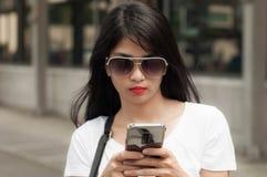 Uma jovem mulher está usando um telefone esperto fotografia de stock royalty free