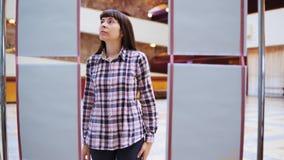 Uma jovem mulher examina a exposição na galeria video estoque