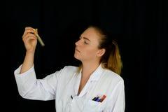 Uma jovem mulher examina os tubos de ensaio Fotos de Stock Royalty Free