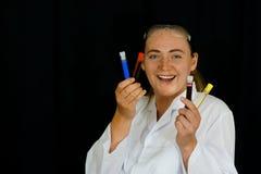 Uma jovem mulher examina os tubos de ensaio Fotos de Stock