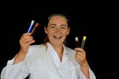 Uma jovem mulher examina os tubos de ensaio Foto de Stock Royalty Free