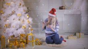 Uma jovem mulher fala em seu telefone sob uma árvore de Natal filme