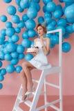 Uma jovem mulher faz um desejo com o bolo que senta-se na escada portátil no fundo cor-de-rosa da parede com bolhas azuis velas 2 Imagem de Stock Royalty Free