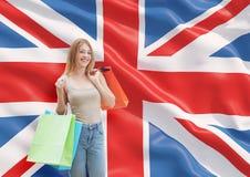 Uma jovem mulher feliz com os sacos de compras coloridos das lojas extravagantes Fotografia de Stock