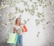 Uma jovem mulher feliz com os sacos de compras coloridos das lojas extravagantes As notas do dólar estão caindo para baixo do tet Imagem de Stock