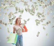 Uma jovem mulher feliz com os sacos de compras coloridos das lojas extravagantes As notas do dólar estão caindo para baixo do tet Fotografia de Stock Royalty Free