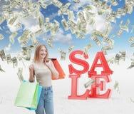 Uma jovem mulher feliz com os sacos de compras coloridos das lojas extravagantes As notas do dólar estão caindo para baixo do céu Foto de Stock