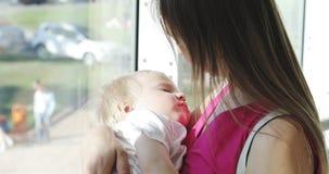 Uma jovem mulher guarda um filho de sono em seus braços video estoque