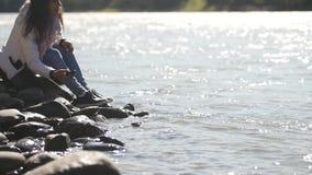Uma jovem mulher joga pedras na água, apreciando um morno, ensolarada, dia do outono vídeos de arquivo