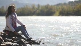 Uma jovem mulher joga pedras na água, apreciando um morno, ensolarada, dia do outono video estoque